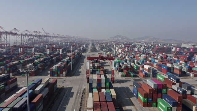 vidéos et rushes de aerial view of containers and container ship in sea - décharger