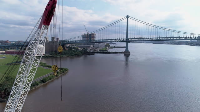 vídeos de stock e filmes b-roll de aerial view of cooper's point park and industrial docks with cranes on the shore of delaware river in camden, new jersey. drone video with the forward camera motion. - ponte ben franklin