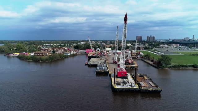 ニュージャージー州カムデンのデラウェア川岸にクレーンを持つクーパーズポイントパークと工業用ドックの空中写真。パノラマ軌道カメラの動きを持つドローンビデオ。 - デラウェア川点の映像素材/bロール