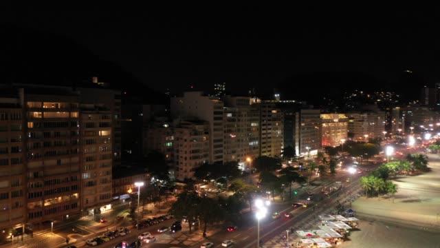 vídeos de stock, filmes e b-roll de vista aérea da praia de copacabana na noite, rio de janeiro - ponto turístico
