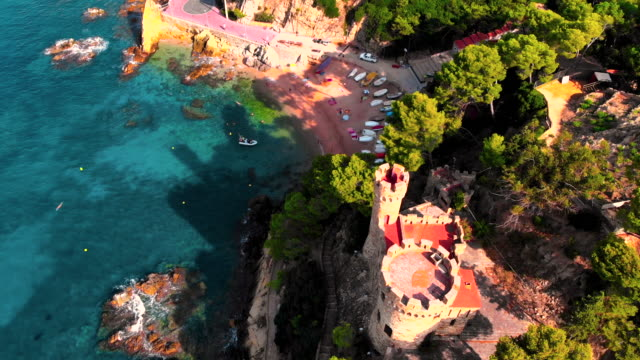 stockvideo's en b-roll-footage met aerial view of costa brava shoreline in summer with castle and stunning landscape in spain. vista aerea del castillo de lloret de mar con su increible costa. - fysische geografie