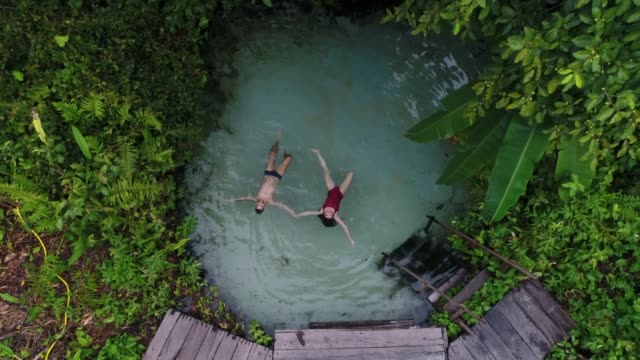 aerial view of couple floating in fervedouro in tocantins, brazil - lagoon stock videos & royalty-free footage