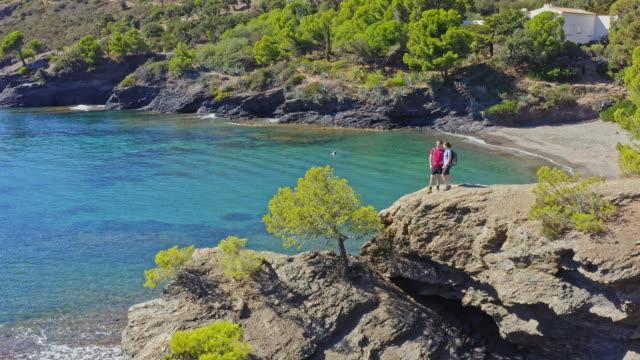 vidéos et rushes de vue aérienne du couple, randonnée dans la côte de costa brava, catalogne - pin
