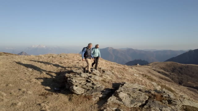 aerial view of couple hiking to viewpoint and taking selfie - attività video stock e b–roll