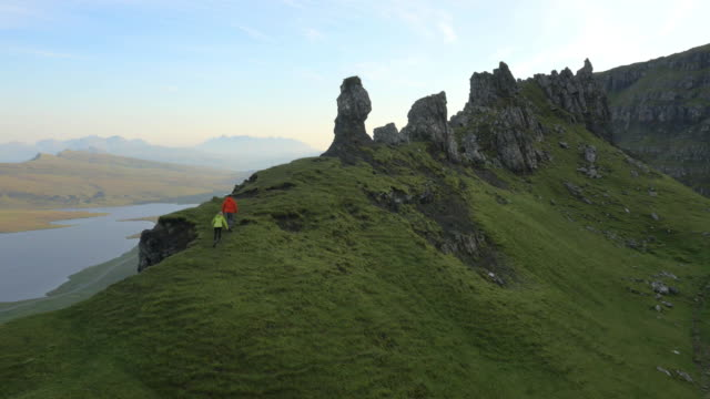aerial view of couple hill walking trotternish ridge - schottisches hochland stock-videos und b-roll-filmmaterial