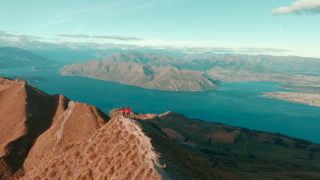 aerial view of couple on mountain top watching viewpoint - hd format stock videos & royalty-free footage