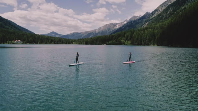 aerial view of couple paddleboarding on river - oar stock videos & royalty-free footage
