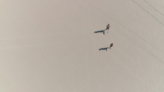 aerial view of couple running in the dessert - surreale video stock e b–roll