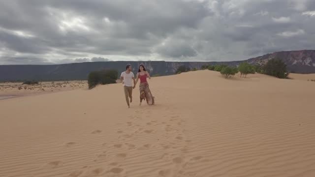 vídeos de stock, filmes e b-roll de vista aérea dos pares que funcionam nas dunas de areia de jalapão, tocantins - discovery