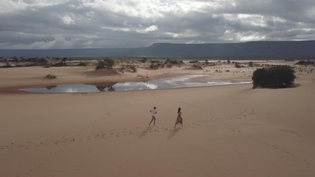 vídeos de stock, filmes e b-roll de vista aérea dos pares que funcionam nas dunas de areia de jalapão, tocantins - footpath