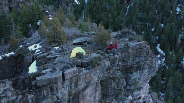 aerial view of couple sitting on cliff ledge in there campsite - american fork canyon点の映像素材/bロール