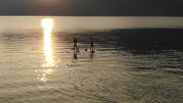 Luftaufnahme des Paares aufstehen paddeln Boarding auf See bei Sonnenaufgang