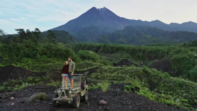aerial view of couple standing   old fashioned suv on the background of merapi volcano - indonesia volcano stock videos & royalty-free footage