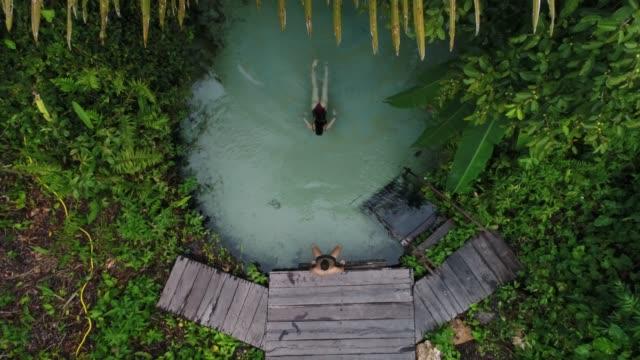 vídeos de stock, filmes e b-roll de vista aérea da natação dos pares em fervedouro em tocantins, brasil - natação