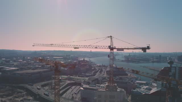 stockvideo's en b-roll-footage met luchtmening van kranen die wolkenkrabbers in göteborg västlänken göta älv brug bouwen - wolkenkrabber