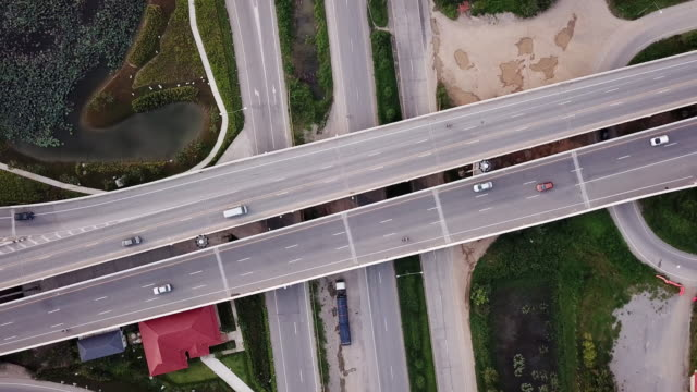 aerial view of crossroad with urban traffic on highway , transportation concept - crossroad stock videos & royalty-free footage