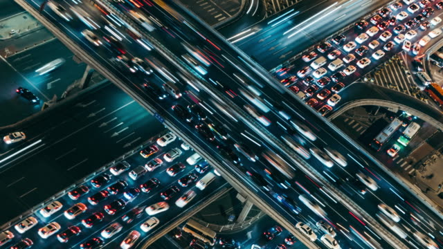 t/l ms ha aerial view of crowded road intersection at rush hour, night - esposizione lunga video stock e b–roll