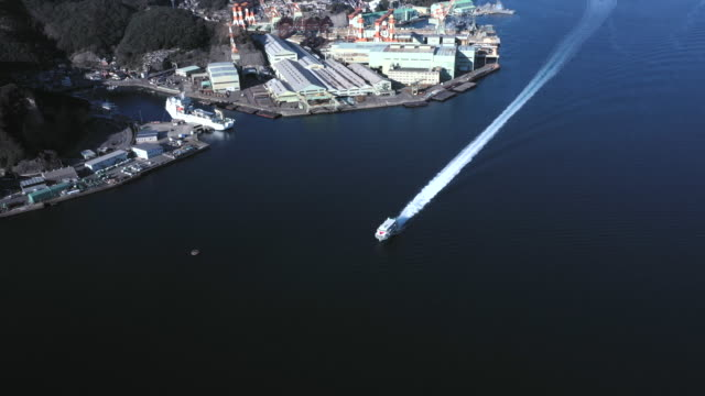 aerial view of cruise ship and port city - 航跡点の映像素材/bロール