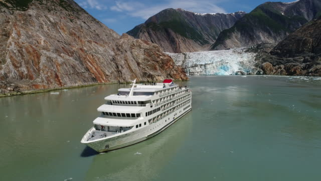 aerial view of cruise ship at sawyer glacier in tracy arm, southeastern alaska - cruising stock videos & royalty-free footage