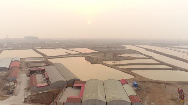 vídeos de stock, filmes e b-roll de aerial view of dagang oil field and smog on march 17 2017 in huanghua china - micrografia científica