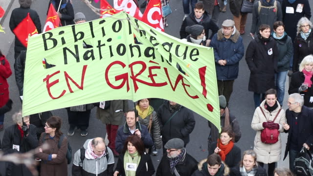 """aerial view of demonstrators with a """"national library on strike"""" banner march during a day of protest and ongoing transport worker strikes over... - reform stock-videos und b-roll-filmmaterial"""