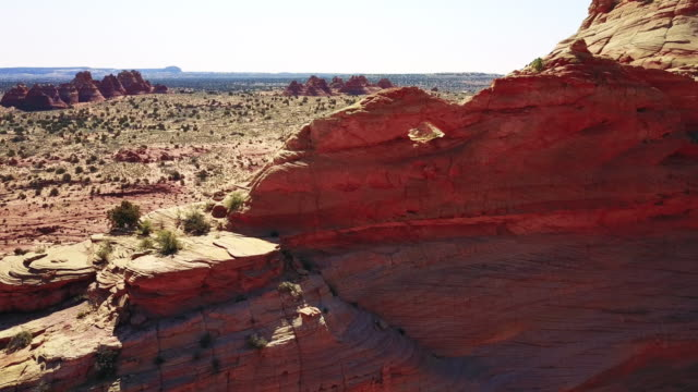 aerial view of desert sand stone arch and cliffs - arch architectural feature stock videos and b-roll footage