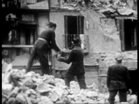 vidéos et rushes de aerial view of destruction caused by fascist bombing / men clearing rubble / destroyed buildings / the bombed socialist newspaper building - guerre