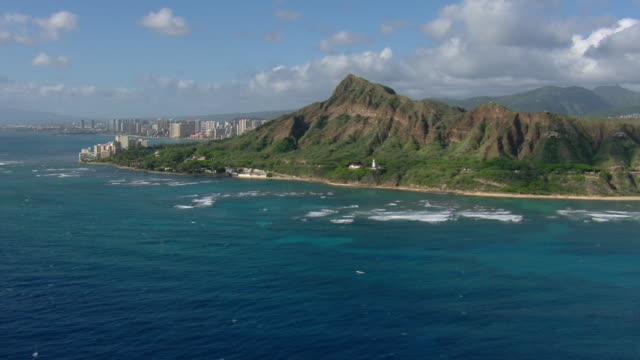 Aerial view of Diamond Head Crater and lighthouse on the coast of Honolulu with distant skyscrapers.