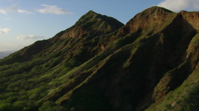 Aerial view of Diamond Head Crater on the coast of Honolulu with distant skyscrapers.