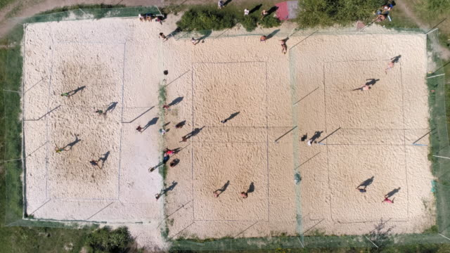 Aerial view of different teams playing volleyball on outdoor playground