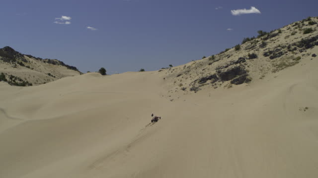 aerial view of distant all-terrain vehicles arriving and climbing sand dune / little sahara, utah, united states - three objects stock videos & royalty-free footage