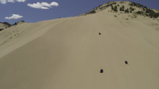 aerial view of distant all-terrain vehicles climbing sand dune / little sahara, utah, united states - three objects stock videos & royalty-free footage