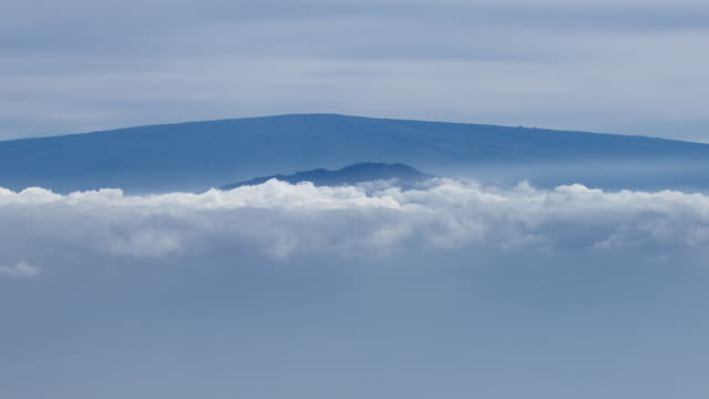 Aerial view of distant volcanic peaks of the Island of Hawaii visible through low clouds.