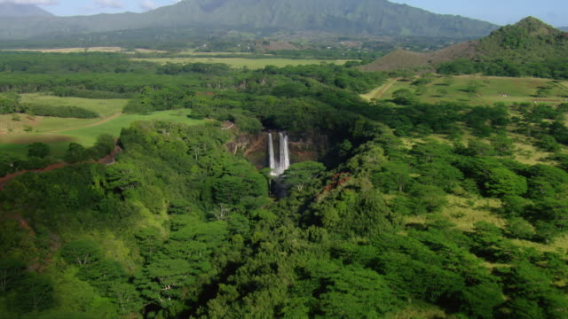 aerial view of distant wailua waterfall and lush countryside of the hawaiian island of kauai. - insel kauai stock-videos und b-roll-filmmaterial