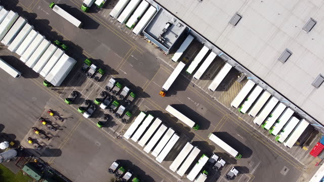 aerial view of distribution warehouse with lorries in loading bays. locked-off shot. - distribution warehouse stock-videos und b-roll-filmmaterial