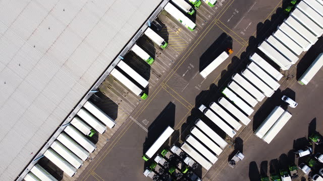 aerial view of distribution warehouse with lorries in loading bays. tracking shot l to r. - commercial land vehicle stock videos & royalty-free footage