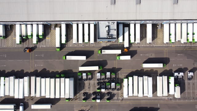 aerial view of distribution warehouse with lorries in loading bays.tracking shot l to r. - real time stock videos & royalty-free footage