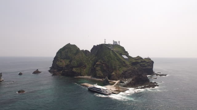 aerial view of dokdo island (natural monument heritage and one of most famous island in korea) and ferry ship at dokdo harbor - north gyeongsang province stock videos and b-roll footage