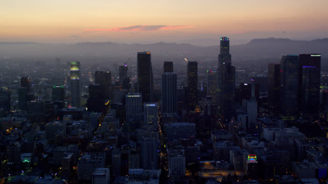 vídeos de stock, filmes e b-roll de aerial view of downtown los angeles at dusk, looking west towards the ocean and the hollywood hills, red r3d 4k - west hollywood