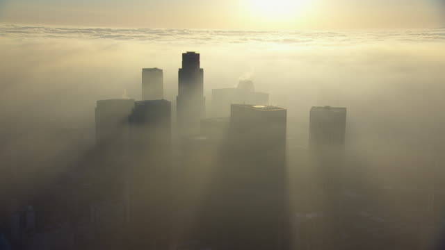 vídeos de stock e filmes b-roll de aerial view of downtown los angeles, shrouded with a thick smog. pollution from cars in this highly populous area combined with geographic particularities contribute to la's notoriously severe air pollution. - nevoeiro