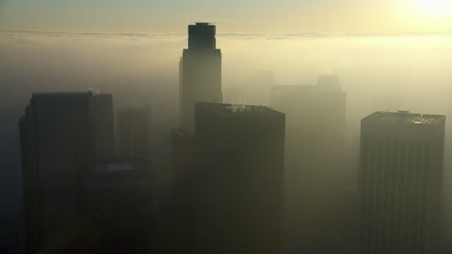 aerial view of downtown los angeles skyscrapers, surrounded by a golden haze. - smog stock videos & royalty-free footage