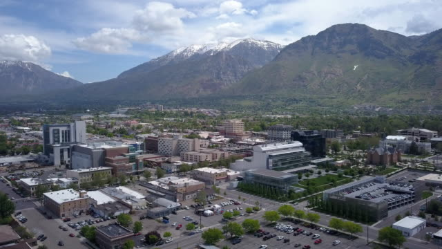aerial view of downtown provo, utah and the wasatch mountains - provo stock-videos und b-roll-filmmaterial