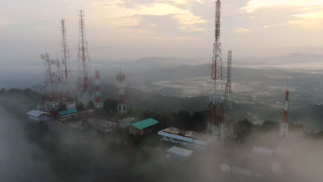 aerial view of drone movie, a telecommunications tower on top of mountain over the white sea of clouds with a fog on cloudy morning - directly below stock videos & royalty-free footage