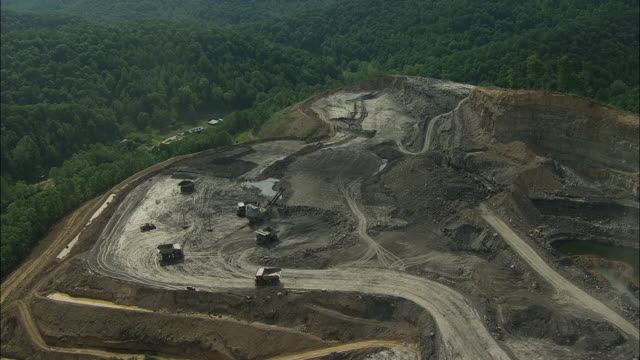 aerial view of dump trucks and excavator at hobet 21 coal mine - coal mine stock videos & royalty-free footage