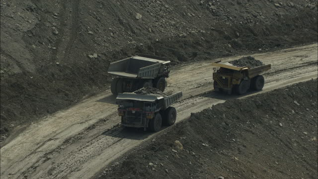 aerial view of dump trucks at hobet 21 coal mine - bergbau stock-videos und b-roll-filmmaterial