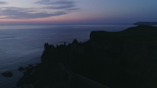 aerial view of dunluce castle ruin at dusk, ireland - 島点の映像素材/bロール