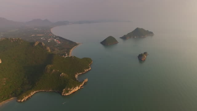 vídeos de stock e filmes b-roll de aerial view of early morning sunrise over the seaside landscape and outlying islands in pranburi, thailand - vista do mar