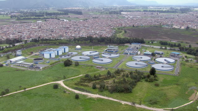 vidéos et rushes de aerial view of el salitre wastewater treatment plant with city and mountain in background, bogota, colombia - écosystème