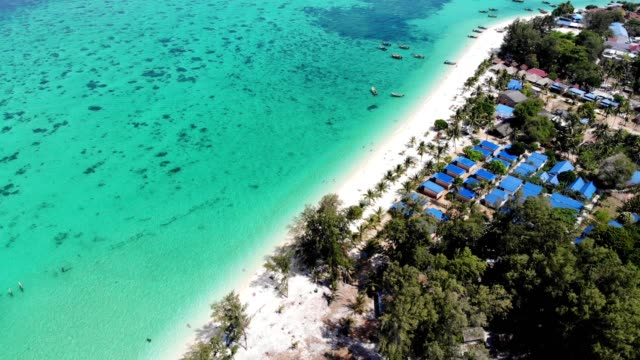 vídeos de stock e filmes b-roll de aerial view of emerald tropical sea with resort on the beach and wooden boats at lipe island - ancora
