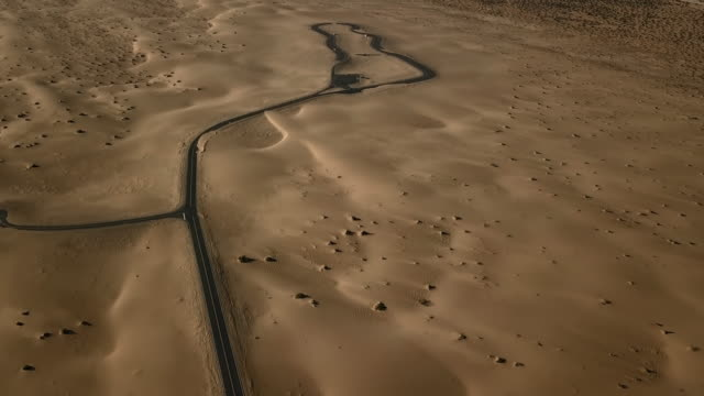 aerial view of empty road in desert and sand dunes - remote location video stock e b–roll